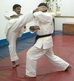 Defender counter-attacks with right roundhouse kick.